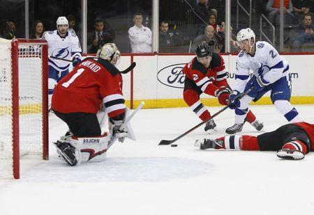 Dec 3, 2018; Newark, NJ, USA; New Jersey Devils goaltender Keith Kinkaid (1) and New Jersey Devils defenseman Ben Lovejoy (12) defend against Tampa Bay Lightning center Brayden Point (21) during first period at Prudential Center. Mandatory Credit: Noah K. Murray-USA TODAY Sports