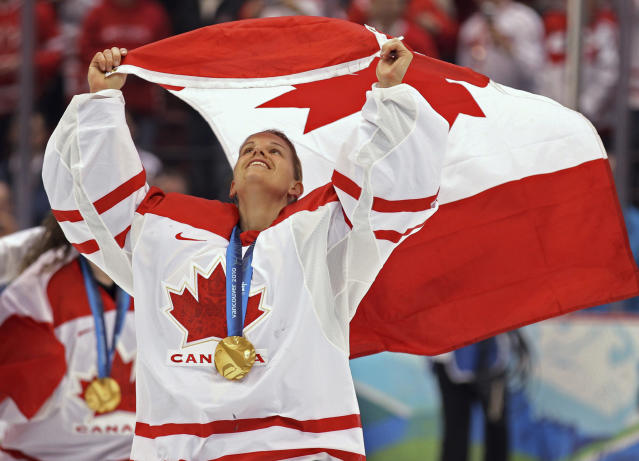 FILE - In this Thursday, Feb. 25, 2010, file photo, Canada's Kim St. Pierre waves the Canadian flag after defeating the USA 2-0 in the women's gold medal final ice hockey at the 2010 Winter Olympic Games in Vancouver, British Columbia. St. Pierre has been elected to the Hockey Hall of Fame's class of 2020. (Jonathan Hayward/The Canadian Press via AP, File)