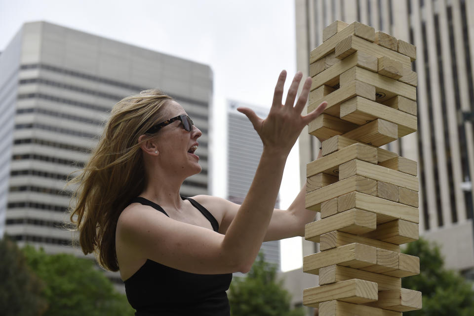 DENVER, CO - JUNE 10: Tammy Muse reacts as a gust of wind knocks over a giant jenga tower before she could make her move at Skyline Park in Denver, Colorado on June 10, 2016. Denver is looking to activate the 16th Street Mall this summer, more so than in previous years. (Photo by Seth McConnell/The Denver Post via Getty Images)