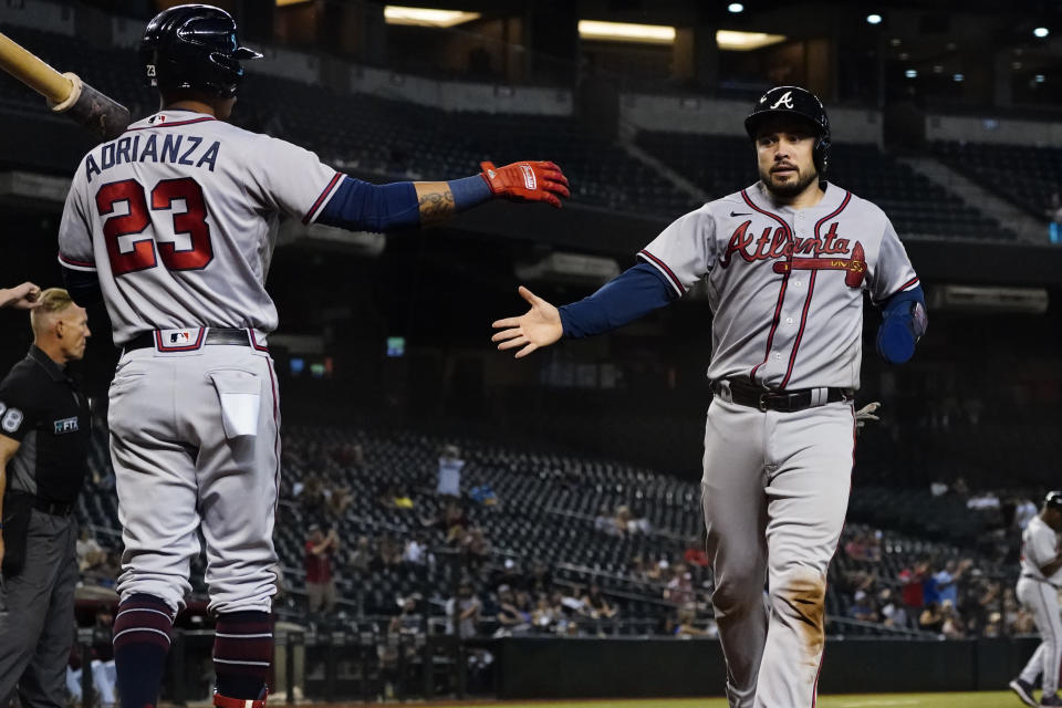 Atlanta Braves' Travis d'Arnaud greets Ehire Adrianza (23) as he scores on a base hit by Dansby Swanson during the ninth inning of a baseball game against the Arizona Diamondbacks, Tuesday, Sept. 21, 2021, in Phoenix. (AP Photo/Matt York)