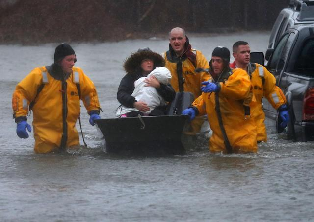 <p>A mother and child are rescued by boat from their home in the Houghs Neck section of Quincy, Mass., during a nor'easter storm on March 2, 2018. (Photo: ohn Tlumacki/The Boston Globe via Getty Images)J </p>
