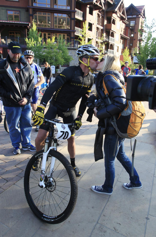 Lance Armstrong kisses girlfriend Anna Hansen as Armstrong prepares to take part in the Power of Four mountain bicycle race at the starting line in Snowmass Village, Colo., early Saturday, Aug. 25, 2012. The race is the first public appearance for Armstrong since the U.S. Anti-Doping Association stripped him of his seven Tour de France championships and banned him for life from the sport. (AP Photo/David Zalubowski)