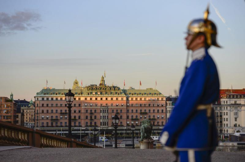 A Palace guard stands in front of the Royal Palace while the sun sinks over the Grand Hotel in downtown Stockholm, Sweden Tuesday Sept.3, 2013, on the eve of the two-day visit by U.S. President Barack Obama. The President is believed to be staying at this hotel. (AP photo / TT News Agency / Henrik Montgomery) ** SWEDEN OUT **