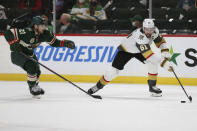 Vegas Golden Knights' Mark Stone (61) controls the puck next to Minnesota Wild's Carson Soucy (21) during the second period in Game 3 of a first-round NHL hockey playoff series Thursday, May 20, 2021, in St. Paul, Minn. (AP Photo/Stacy Bengs)