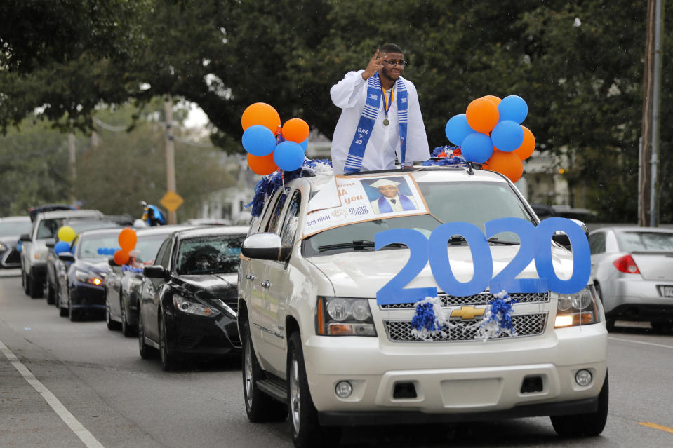 Graduates of New Orleans Charter Science and Math High School class of 2020 parade in vehicles after holding a drive-in graduation ceremony as a result of the COVID-19 pandemic, outside Delgado Community College in New Orleans, Wednesday, May 27, 2020. Students and family got out of their cars to receive diplomas one by one, and then held a parade of cars through city streets. (AP Photo/Gerald Herbert)