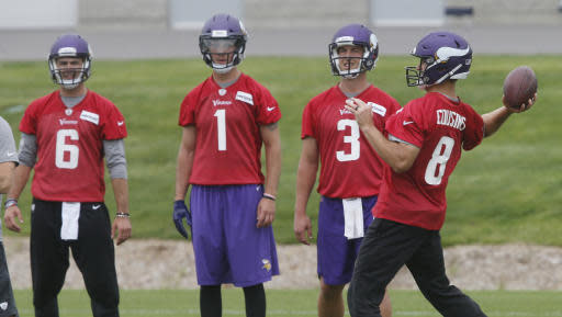 Minnesota Vikings quarterback Kirk Cousins, right, throws as fellow quarterbacks, from left, Peter Pujals, Kyle Sloter, and Trevor Siemian watch during NFL football team's training camp in Eagan, Minn.,Tuesday, June 12, 2018. (AP Photo/Jim Mone)