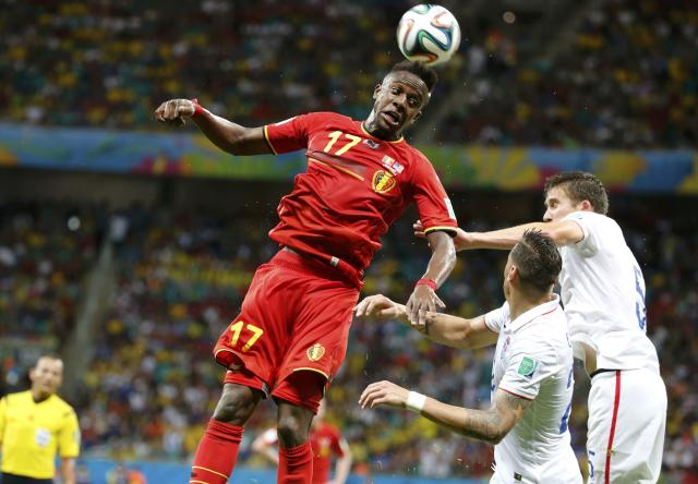 Belgium's Divock Origi jumps for the ball next to Geoff Cameron and Matt Besler (R) of the U.S. during their 2014 World Cup round of 16 game at the Fonte Nova arena in Salvador July 1, 2014. REUTERS/Sergio Moraes (BRAZIL - Tags: SOCCER SPORT WORLD CUP TPX IMAGES OF THE DAY)