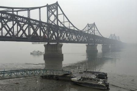 Trucks move across the bridge linking North Korea with the Chinese border city of Dandong