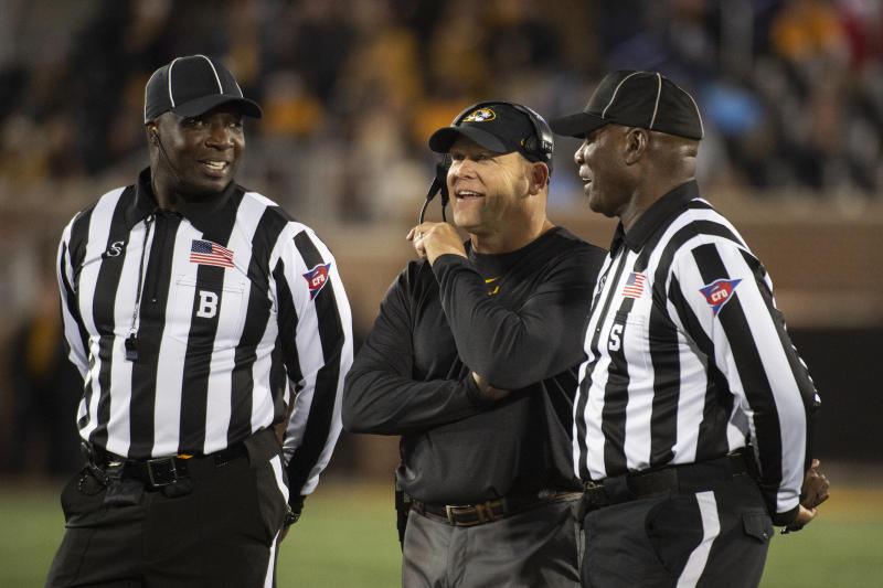 Missouri head coach Barry Odom, center, laughs while talking with referees during the second quarter of an NCAA college football game against Mississippi Saturday, Oct. 12, 2019, in Columbia, Mo. (AP Photo/L.G. Patterson)