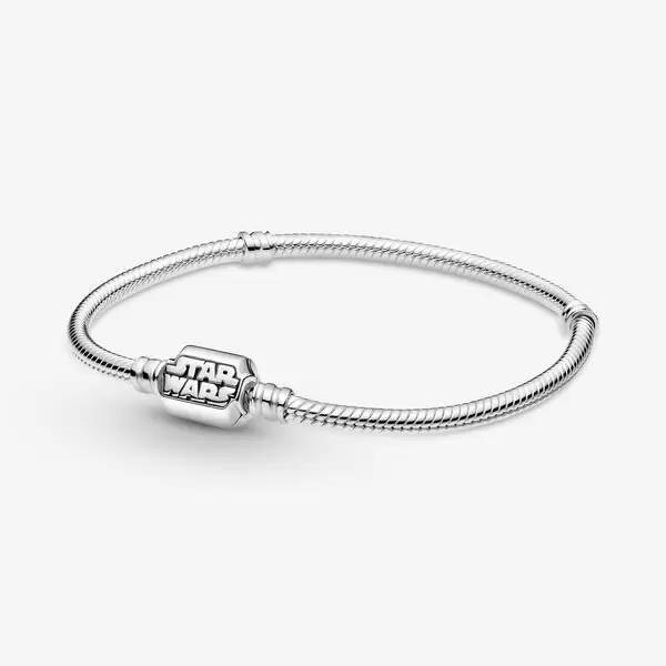 """<p><strong>Pandora Moments</strong></p><p>pandora.net</p><p><strong>$95.00</strong></p><p><a href=""""https://go.redirectingat.com?id=74968X1596630&url=https%3A%2F%2Fus.pandora.net%2Fen%2Fjewelry%2Fbracelets%2Fcharm-bracelets%2Fpandora-moments-star-wars-snake-chain-clasp-bracelet%2F599254C00.html&sref=https%3A%2F%2Fwww.goodhousekeeping.com%2Fholidays%2Fgift-ideas%2Fg29624061%2Fstar-wars-gifts%2F"""" rel=""""nofollow noopener"""" target=""""_blank"""" data-ylk=""""slk:Shop Now"""" class=""""link rapid-noclick-resp"""">Shop Now</a></p><p>As you venture across the galaxy collecting charms, the best place to keep thm is this Pandora bracelet. It's the perfect place to hold a <a href=""""https://go.redirectingat.com?id=74968X1596630&url=https%3A%2F%2Fus.pandora.net%2Fen%2Fjewelry%2Fcharms%2Fcharms%2Fstar-wars-grogu-charm%2F799253C01.html&sref=https%3A%2F%2Fwww.goodhousekeeping.com%2Fholidays%2Fgift-ideas%2Fg29624061%2Fstar-wars-gifts%2F"""" rel=""""nofollow noopener"""" target=""""_blank"""" data-ylk=""""slk:Grogu"""" class=""""link rapid-noclick-resp"""">Grogu</a> or <a href=""""https://go.redirectingat.com?id=74968X1596630&url=https%3A%2F%2Fus.pandora.net%2Fen%2Fjewelry%2Fcharms%2Fcharms%2Fstar-wars-shining-3d-logo-charm---final-sale%2F769247C01.html&sref=https%3A%2F%2Fwww.goodhousekeeping.com%2Fholidays%2Fgift-ideas%2Fg29624061%2Fstar-wars-gifts%2F"""" rel=""""nofollow noopener"""" target=""""_blank"""" data-ylk=""""slk:logo charm"""" class=""""link rapid-noclick-resp"""">logo charm</a>. </p>"""