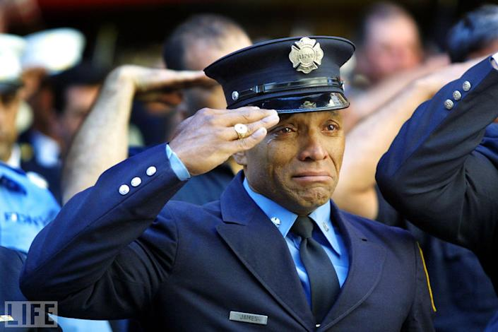 """On 9/11, the New York City Police Department lost 23 officers. The Port Authority police lost 37. The FDNY's dead numbered 343. Here, firefighter Tony James cries while attending the funeral service for New York Fire Department chaplain Mychal Judge at New York's St. Francis of Assisi Church, September 15, 2001. Photographer Joe Raedle, who attended and photographed funerals for weeks after September 11, told LIFE.com of this shot: """"Anytime you see a fireman or a symbol of strength breaking down like that, it resonates."""" In fact, Raedle's photograph, with its ghostly echoes of James' salute surrounding his tear-streaked face, speaks to how millions of people around the world felt in the days and weeks after the attacks: namely, that strength was what we all needed most, and that it was the one thing that was hardest to find. <br><br>(Photo: Joe Raedle/Getty Images )<br><br>For the full photo collection, go to <a href=""""http://www.life.com/gallery/59971/911-the-25-most-powerful-photos#index/0"""" rel=""""nofollow noopener"""" target=""""_blank"""" data-ylk=""""slk:LIFE.com"""" class=""""link rapid-noclick-resp"""">LIFE.com</a>"""