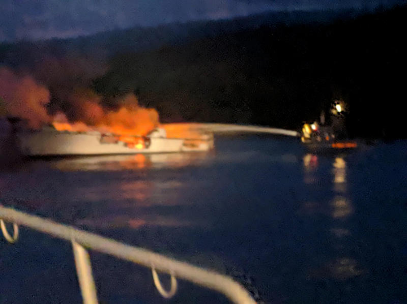 In this photo provided by the Santa Barbara County Fire Department, firefighters work to extinguish a dive boat engulfed in flames after a deadly fire broke out aboard the commercial scuba diving vessel off the Southern California Coast Monday morning, Sept. 2, 2019. (Santa Barbara County Fire Department via AP)
