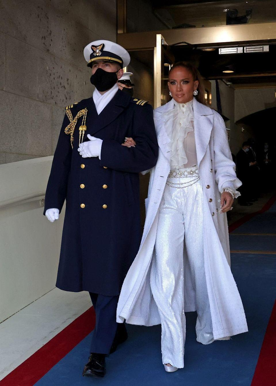 """<p>White clothing has historically paid homage to the women's suffrage movement in America, and Jennifer Lopez rocked her all-white <a href=""""https://www.chanel.com/us/"""" rel=""""nofollow noopener"""" target=""""_blank"""" data-ylk=""""slk:Chanel"""" class=""""link rapid-noclick-resp"""">Chanel</a> pantsuit while performing a version of <em>This Land Is Your Land </em>after Joe Biden's swearing-in as the 46th President of the United States. The look included pieces shown at <a href=""""https://www.veranda.com/luxury-lifestyle/luxury-fashion-jewelry/a34918791/chateau-de-chenonceau/"""" rel=""""nofollow noopener"""" target=""""_blank"""" data-ylk=""""slk:Chanel's 2020 Metier d'Arts show"""" class=""""link rapid-noclick-resp"""">Chanel's 2020 Metier d'Arts show</a>, which was held at Chenonceau.</p>"""