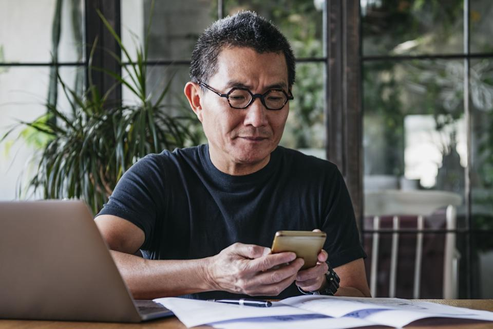 Asian man in his 50s working remotely, using mobile phone, communication, connections, technology