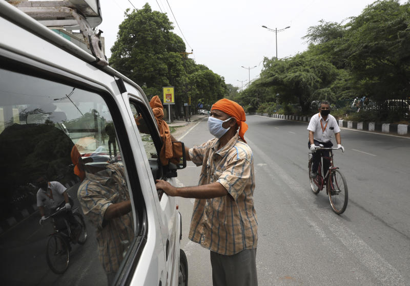 In this June 4, 2020, photo, Indian driver Gangaram, 48, who lost his job and business because of the coronavirus lockdown cleans his vehicle in New Delhi, India. Gangaram used to pick and drop schoolchildren from a New Delhi neighborhood. The job assured him of slim financial security. to relaunch the economy. That's the harsh truth facing workers laid off around the world, from software companies in Israel to restaurants in Thailand and car factories in France, whose livelihoods fell victim to a virus-driven recession that's accelerating decline in struggling industries and upheaval across the global workforce. (AP Photo/Manish Swarup)
