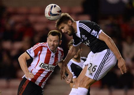 Sunderland's Phil Bardsley (L) challenges Southampton's Jos Hooiveld during their English League Cup fourth round soccer match at the Stadium of Light in Sunderland, November 6, 2013. REUTERS/Nigel Roddis
