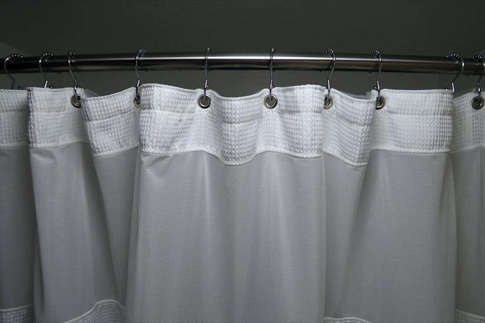 white shower curtain on curved rod