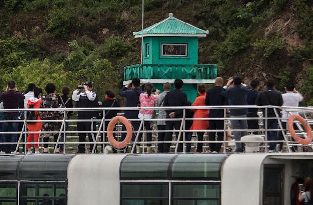 <p>Chinese tourists look and take pictures of a North Korean soldier in a watchtower as they ride on a tourist boat on the Yalu river with North Korean territory on both sides, north of the border city of Dandong, Liaoning province, northern China near Sinuiju, North Korea on May 23, 2017 in Dandong, China. (Photo: Kevin Frayer/Getty Images) </p>
