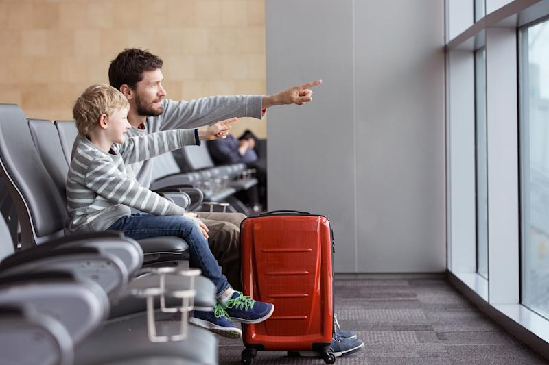 positive smiling boy and his father waiting at the airport for plane departure and pointing with fingers at something, vacation and travel concept
