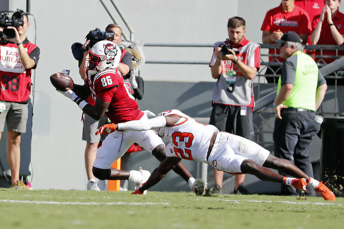 North Carolina State's Emeka Emezie (86) hauls in a pass for a touchdown over Clemson's Andrew Booth Jr. (23) during the first half of an NCAA college football game in Raleigh, N.C., Saturday, Sept. 25, 2021. (AP Photo/Karl B DeBlaker)