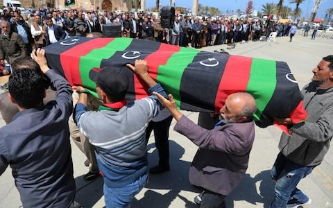 People carry a flag draped coffin of a victim of an overnight shelling, during a funeral at Martyrs' Square in Tripoli - Credit:  HANI AMARA/Reuters