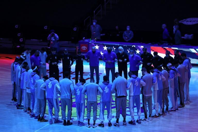 The Los Angeles Lakers and the San Antonio Spurs lock arms during the national anthem prior to a game at Staples Center in response to Wednesday's riots by a mob of President Donald Trump's supporters on the US Capitol Hill