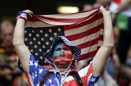 A US fan holds a flag prior to the group G World Cup soccer match between the USA and Germany at the Arena Pernambuco in Recife, Brazil, Thursday, June 26, 2014. (AP Photo/Petr David Josek)