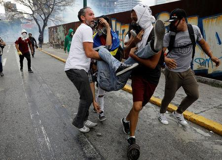A injured demonstrator is helped by others during a rally against Venezuela's President Nicolas Maduro's government in Caracas, Venezuela. REUTERS/Carlos Garcia Rawlins