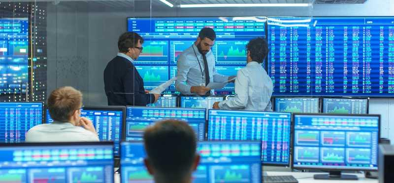 Five traders in a room full of computers with ticker symbols.