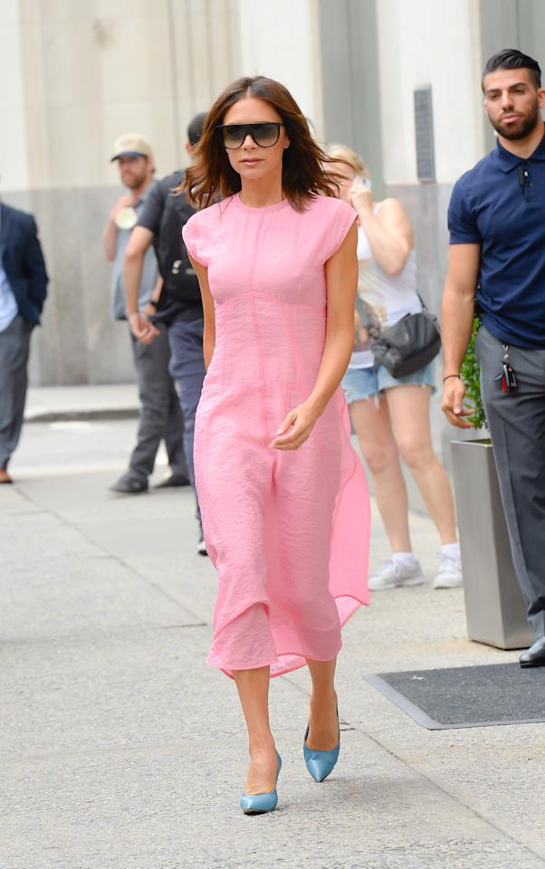 <p>Victoria Beckham's blush pink dress from her own collection was a hit with fashion critics when she was spotted wearing it with blue shoes in New York. [Photo: Getty] </p>