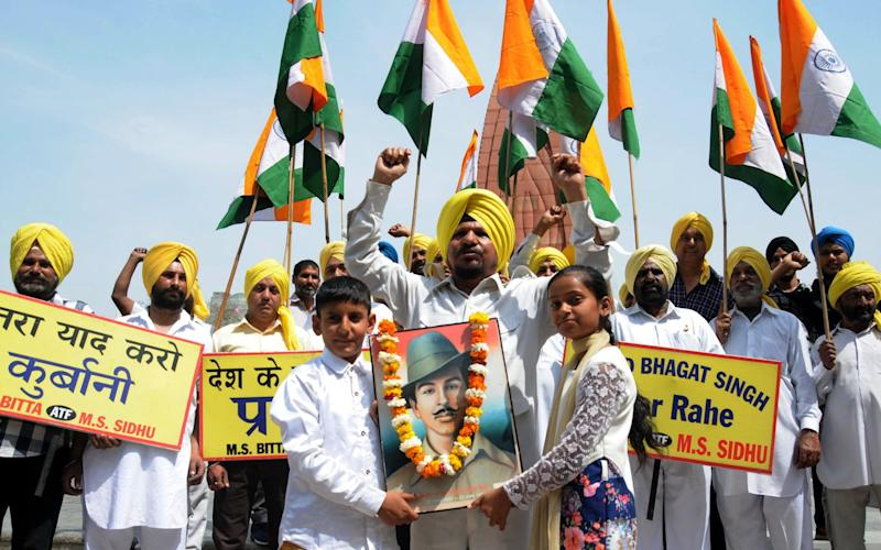 Activists of the All India Anti-Terrorist Front (AIATF) shout patriotic slogans holding Indian flags as children hold portrait of Indian martyr Bhagat Singh  - Credit: EPA