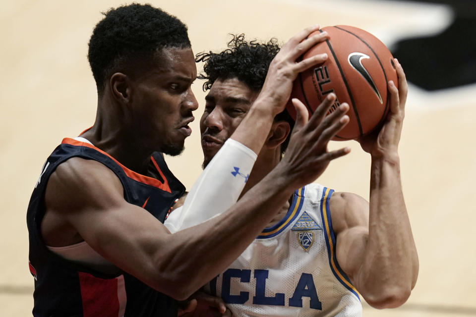 UCLA guard Jules Bernard, right, tries to get past Pepperdine center Victor Ohia Obioha during the second half of an NCAA college basketball game Friday, Nov. 27, 2020, in San Diego. (AP Photo/Gregory Bull)