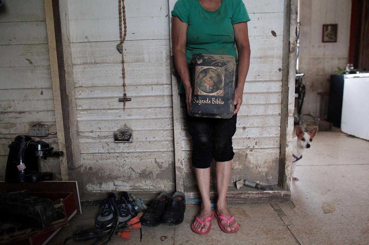 <p>Aurea Esther Gonzalez holds a bible dirty with mud, after Hurricane Maria hit the island in September, in Toa Baja, Puerto Rico, Oct. 18, 2017. (Photo: Alvin Baez/Reuters) </p>