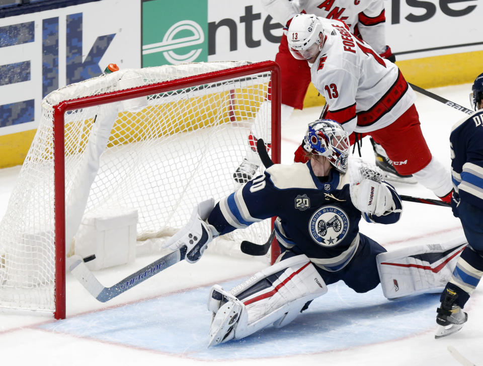 Carolina Hurricanes forward Warren Foegele, right, scores past Columbus Blue Jackets goalie Joonas Korpisalo during the second period of an NHL hockey game in Columbus, Ohio, Sunday, Feb. 7, 2021. (AP Photo/Paul Vernon)