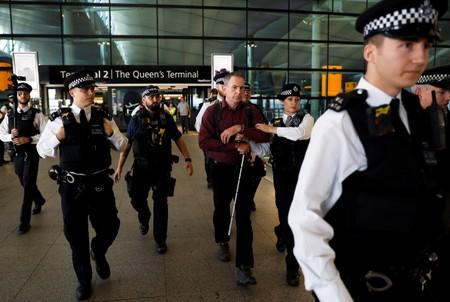 Police officers detain environmental activist James Brown at Heathrow Terminal 2, after climate change protesters tried to launch drones within the airport's exclusion zone, in London