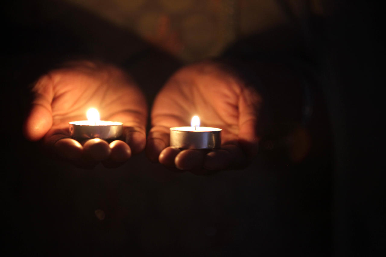 A mourner holds two candles during a vigil at the Sikh Religious Society of Wisconsin for the victims of the shooting at the Sikh Temple of Wisconsin the previous day, on August 6, 2012 in Brookfield, Wisconsin. Wade Michael Page opened fire with a 9mm pistol at the Sikh Temple killing six people before being killed by police in a shootout. (Photo by Darren Hauck/Getty Images)