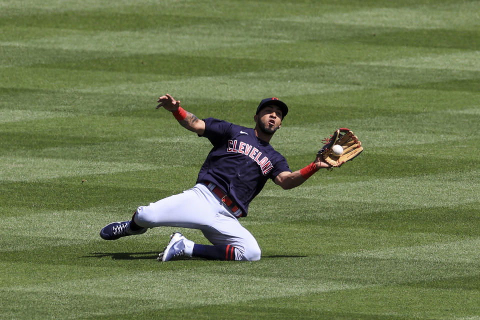 Cleveland Indians' Eddie Rosario makes a catch for an out during the fifth inning of a baseball game in Cincinnati, Sunday, April 18, 2021. (AP Photo/Aaron Doster)