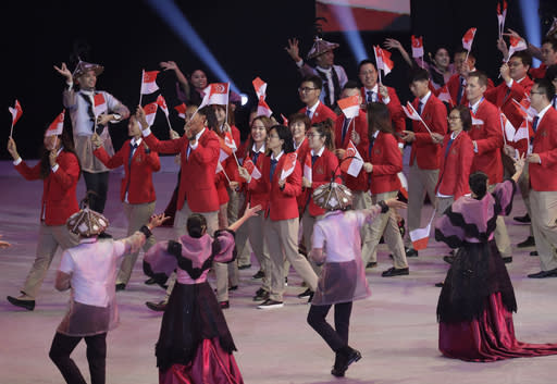 Singapore delegates wave flags during the opening ceremony of the 30th South East Asian Games at the Philippine Arena, Bulacan province, northern Philippines on Saturday, Nov. 30, 2019. (AP Photo/Aaron Favila)