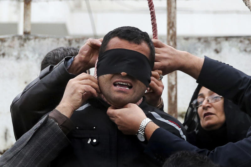 This picture provided by ISNA, a semi-official news agency, taken on Tuesday, April 15, 2014 shows Samereh Alinejad, right, and her husband Abdolghani, left, removing the noose from the neck of blindfolded Bilal who was convicted of murdering their son Abdollah in the northern city of Nour, Iran. Bilal who was convicted of killing Abdollah Hosseinzadeh, was pardoned by the victim's family moments before being executed. (AP Photo/ISNA, Arash Khamoushi)