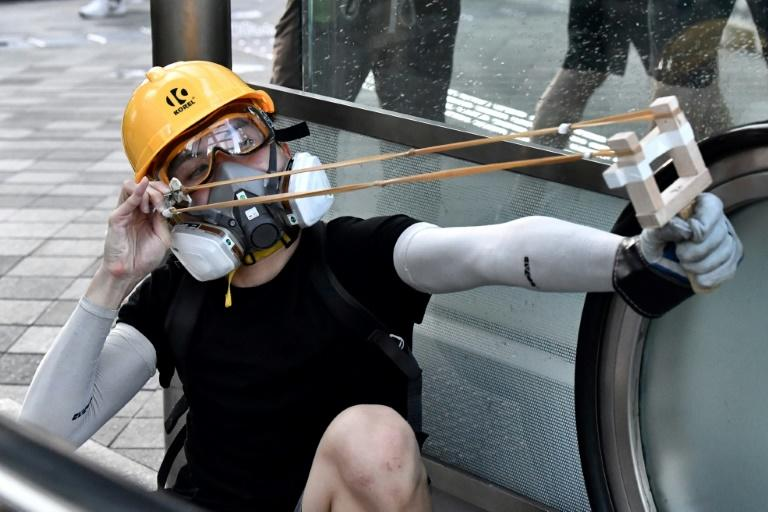 A Hong Kong protester uses an improvised slingshot at police in the city's Admiralty area during a general strike on August 5, 2019