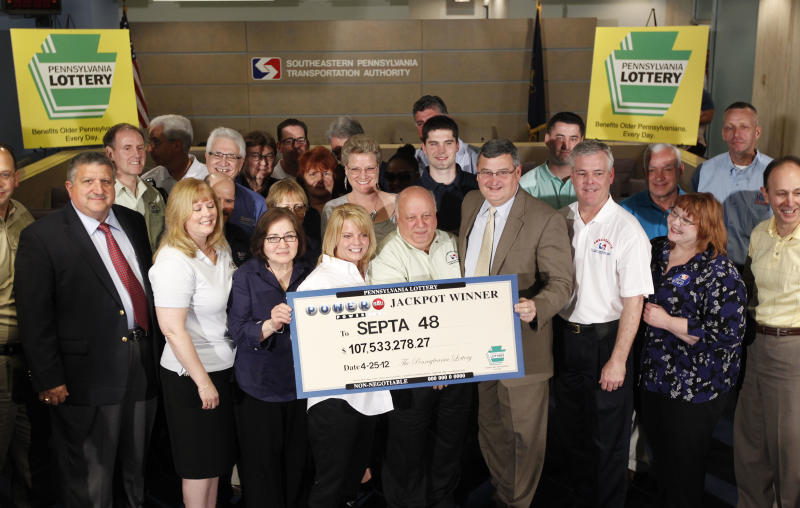 Most of the forty plus Southeastern Pennsylvania Transportation Authority employees who won the Powerball lottery pose for photographs with a ceremonial check during a news conference, Friday, May 4, 2012, in Philadelphia. According to Pennsylvania Lottery officials the prize has a cash value of $107.5 million. (AP Photo/Matt Rourke)
