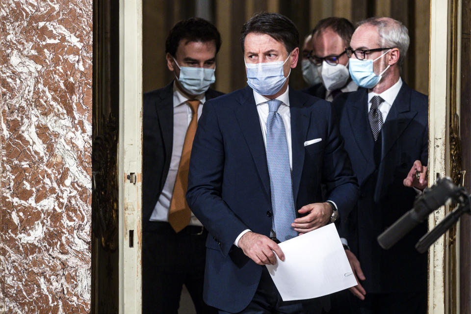 """Italian Premier Giuseppe Conte arrives to announce new restrictions to curb the spread of coronavirus, in Rome, Wednesday, Nov. 4, 2020. Four regions in Italy are being put under severe lockdown, forbidding people to leave their homes except for essential reasons such as food shopping and work in a bid to slow surging COVID-19 infections and prevent hospitals from being overwhelmed. Premier Giuseppe Conte on Wednesday night announced what he described as """"very stringent"""" restrictions on the so-called """"red zone"""" regions of high risk: Lombardy, Piedmont, Valle d'Aosta in the north and Calabria, the region forming the """"toe"""" in the south of the Italian peninsula. (Angelo Carconi/Pool Photo via AP)"""