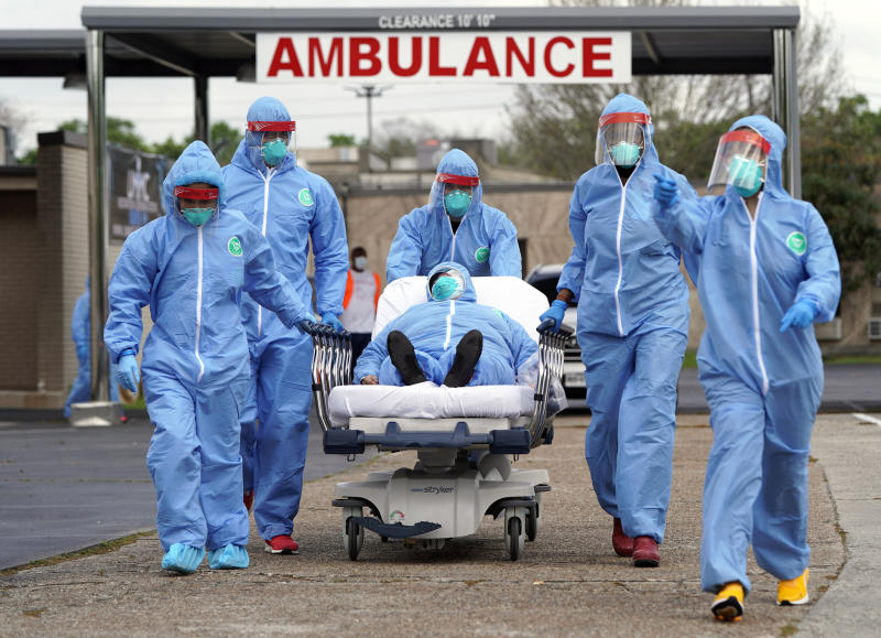 In Houston, a patient is taken by stretcher into the United Memorial Medical Center after going through testing for COVID-19. Cars were lined up for more than two miles, as people awaited coronavirus tests at a drive-thru testing station. (AP Photo/David J. Phillip)