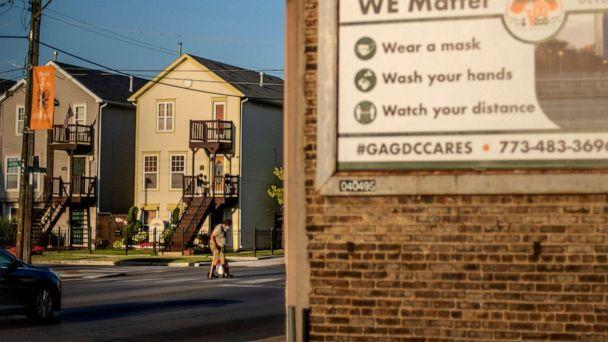 PHOTO: An elderly man crosses the street in the Auburn Gresham neighborhood next to a billboard promoting safety measures against COVID-19 in Chicago, Aug. 27, 2020. (David Goldman/AP, FILE)