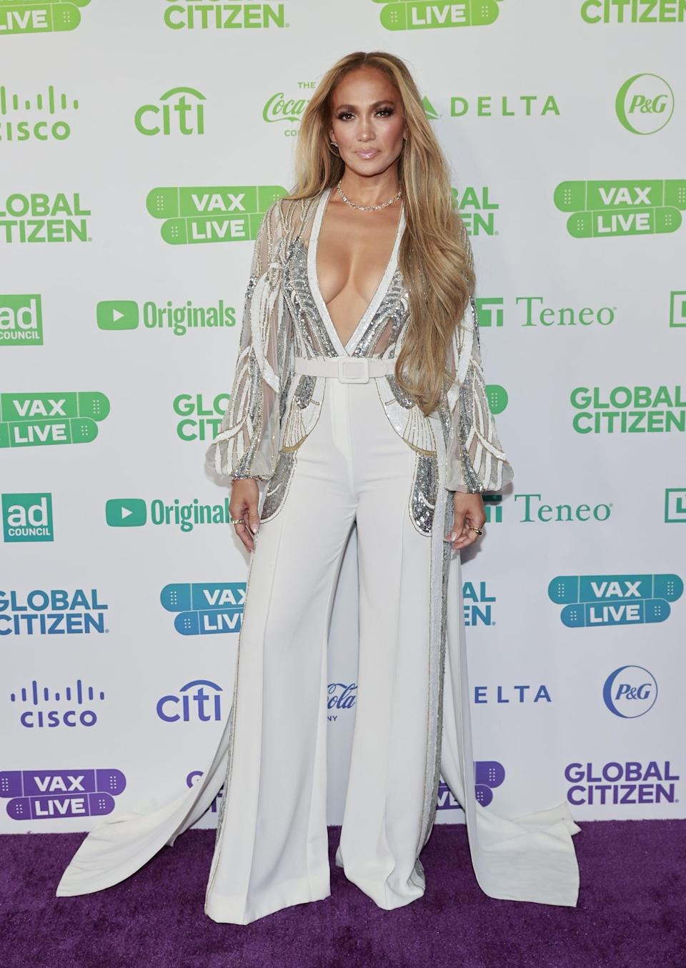 <p>The fall/winter 2021 Elie Saab white, crepe jumpsuit featured a sequin embroidered bodice, which glimmered alongside Lopez's Vrai jewels.</p>