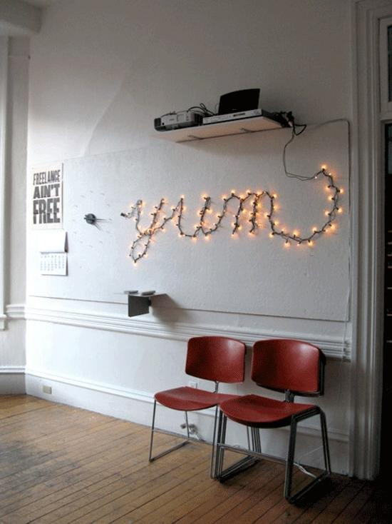"""<div class=""""caption-credit""""> Photo by: Sarah Rainwater via Apartment Therapy</div><b>Light Up Some Words</b> <br> Neon lighting can be expensive - so why not create your own neon-style light with a few pin nails and string lights! You can switch up what it says based on the season or your mood."""
