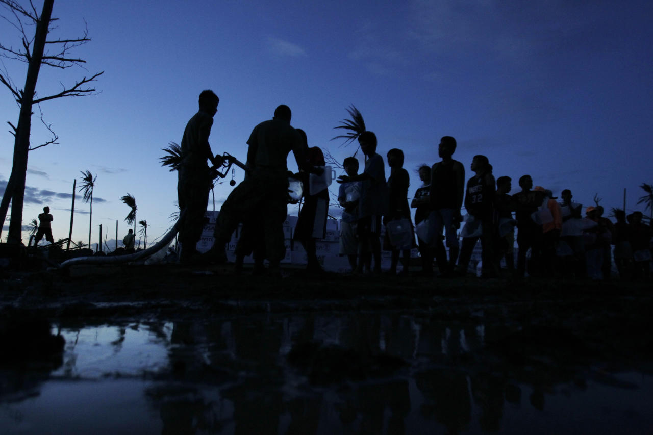 U.S. Marines supply drinking water for typhoon survivors at dusk in Palo, central Philippines, Tuesday, Nov. 19, 2013. Hundreds of thousands of people were displaced by Typhoon Haiyan, which tore across several islands in the eastern Philippines on Nov. 8. (AP Photo/Wally Santana)