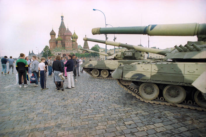 FILE - In this Monday, Aug. 19, 1991 file photo, Groups of people wander among the half dozen Soviet tanks parked behind the Red Square with St. Basil's Cathedral in the background, near the bank of the Moscow River, Russia. When a group of top Communist officials ousted Soviet leader Mikhail Gorbachev 30 years ago and flooded Moscow with tanks, the world held its breath, fearing a rollback on liberal reforms and a return to the Cold War confrontation. But the August 1991 coup collapsed in just three days, precipitating the breakup of the Soviet Union that plotters said they were trying to prevent. (AP Photo/Boris Yurchenko, File)
