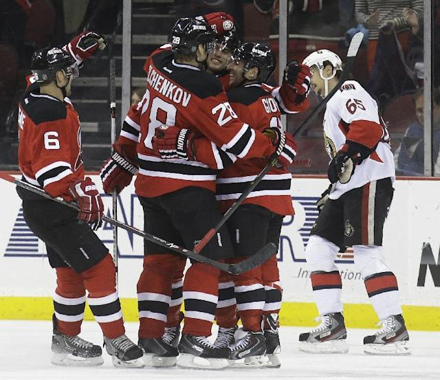 New Jersey Devils right wing Stephen Gionta, center right, is congratulated by teammates Andy Greene (6), Anton Volchenkov (28), of Russia, and Adam Henrique after scoring a goal against the Ottawa Senators during the first period of an NHL hockey game, Wednesday, Dec. 18, 2013, in Newark, N.J. (AP Photo/Julio Cortez)