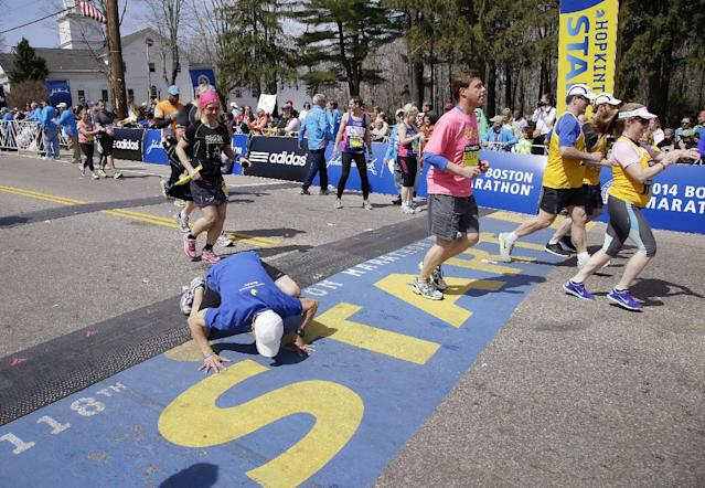 A runner toward the back of the fourth and last wave of competitors kneels to kiss the start line as he begins his running of the 118th Boston Marathon, Monday, April 21, 2014, in Hopkinton, Mass. (AP Photo/Stephan Savoia)